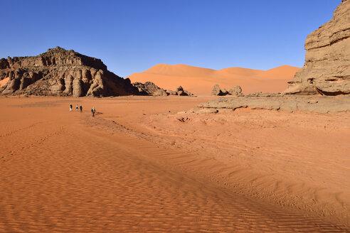 Algeria, Sahara, Tassili N'Ajjer National Park, People hiking between rocks and dunes of Tin Merzouga - ES000890