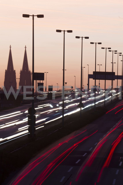Germany, North Rhine-Westphalia, Cologne Cathedral and road traffic on lighted Zoobruecke at dusk - JATF000522