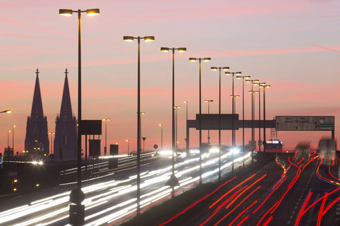 Germany, North Rhine-Westphalia, Cologne Cathedral and road traffic on lighted Zoobruecke at dusk - JATF000523