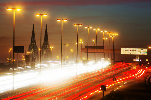 Germany, North Rhine-Westphalia, Cologne Cathedral and road traffic on lighted Zoobruecke at dusk - JAT000524