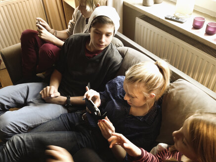 teenagers sitting on a couch playing with electronic devices, Germany, Hamburg - SEF000376