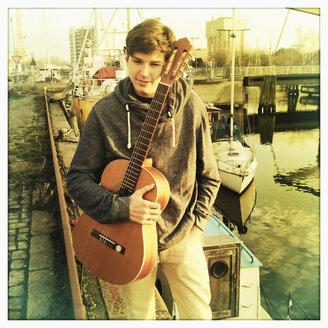 boy holding his guitar on a quai wall, Germany, Hamburg - SEF000309