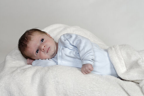 Three weeks old baby boy lying on white woollen blanket - LB000468