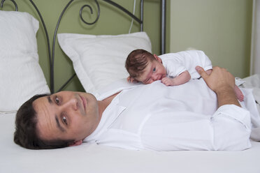 Father with newborn daughter lying on bed - PA000190