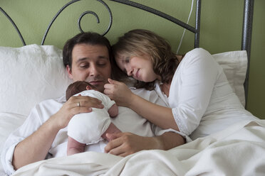 Parents with newborn baby girl lying on bed - PA000192