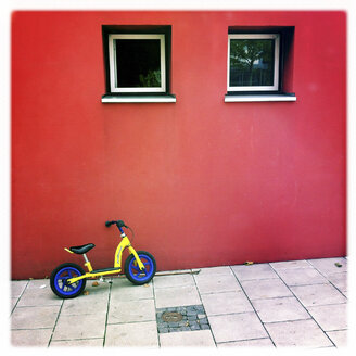 Child's bicycle on house wall, Munich, Germany - GSF000581