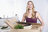 Smiling young woman carrying cardboard box - PDF000612