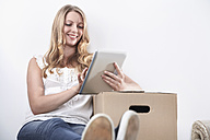 Smiling young woman with cardboard box and tablet computer - PDF000603