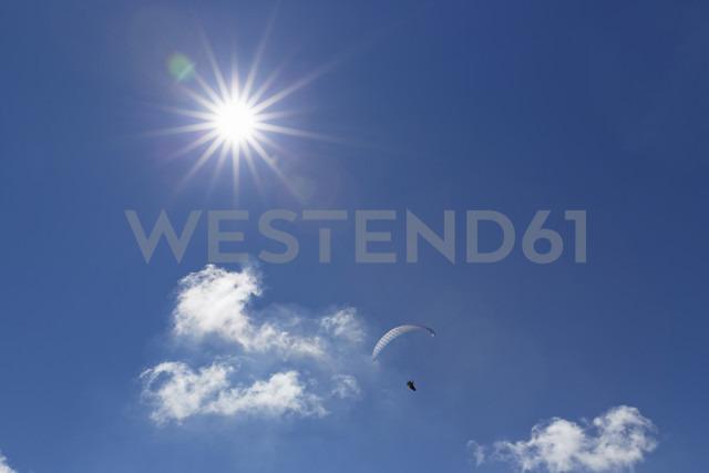 Germany, Bavaria, Upper Bavaria, Isarwinkel, paraglider against the sun - SIE004934