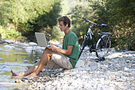 Austria, Salzkammergut, Mondsee, young man with laptop learning at a brook - WWF003189