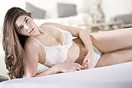 Smiling young woman wearing white bra and panties lying on bed - MAEF007624