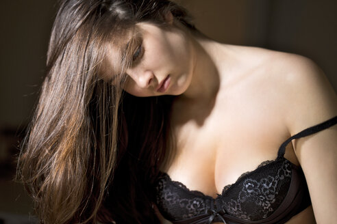 Portrait of thoughtful young woman wearing black bra - MAEF007581