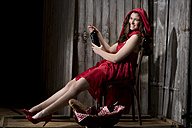 Young woman sitting in a shack dressed as Red Riding Hood, studio shot - MAEF007586