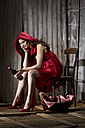 Young woman sitting in a shack dressed as Red Riding Hood, studio shot - MAEF007587