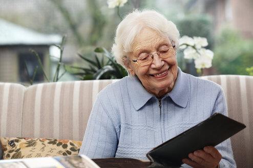 Smiling senior women watching old photographs at home - BIF000267