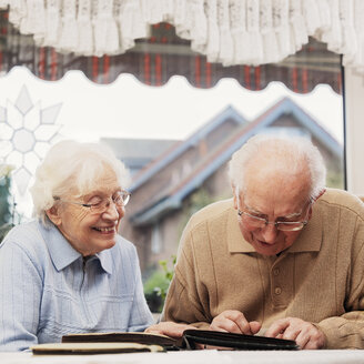 Senior couple watching old photographs at home - BIF000269