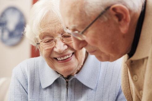 Senior couple watching old photographs at home - BIF000271