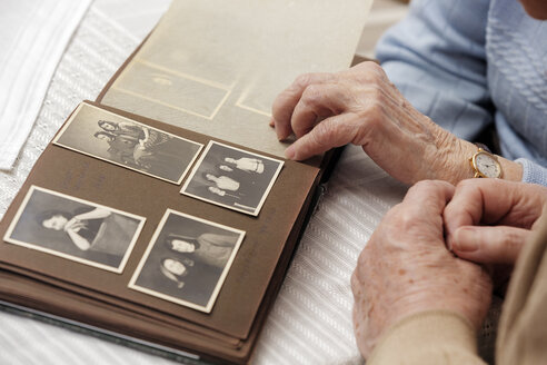 Senior couple watching old photograph album at home - BIF000273