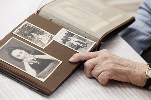 Senior woman watching old photographs of herself - BIF000276