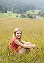 Austria, Salzkammergut, Mondsee, young woman sitting in a meadow - WWF003176