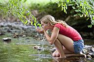 Austria, Salzkammergut, Mondsee, young woman refreshing at a brook - WWF003183