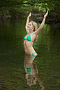Austria, Salzkammergut, Mondsee, young woman with outstretched arms standing in a brook - WWF003186