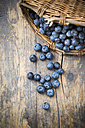 Part of wickerbasket with blueberries (Vaccinium myrtillus) on wooden table - LVF000433