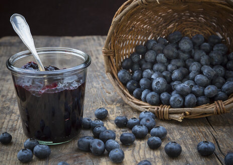 Wickerbasket with blueberries (Vaccinium myrtillus) and glass of blueberry jam on wooden table - LVF000430