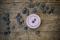 Blueberries (Vaccinium myrtillus) and glass of blueberry yoghurt on wooden table - LVF000428