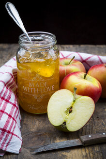 Glass of selfmade apple jam, dish towel and apples on wooden table - LVF000418