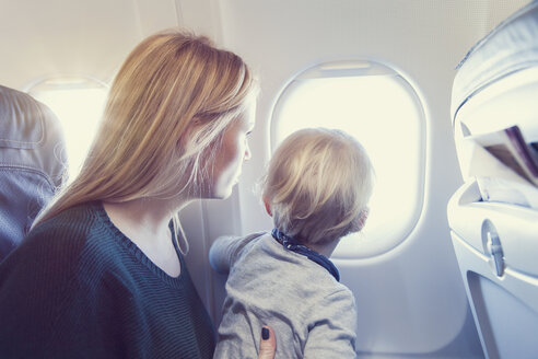 Mother with son in airplane looking out of window - MF000720