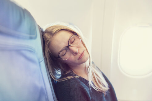 Young woman sleeping in airplane - MF000725