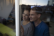 Smiling couple behind window - RBF001594
