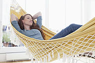 Woman relaxing in a hammock in her apartment - RBF001545