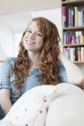 Portrait of young woman relaxing on couch in her apartment - RBF001554