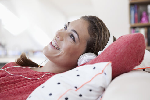 Portrait of woman with headphones lying on a couch in her apartment - RBF001562