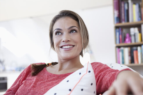 Portrait of smiling woman relaxing on a couch in her apartment - RBF001564
