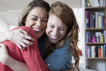 Two young female friends at home embracing - RBF001572