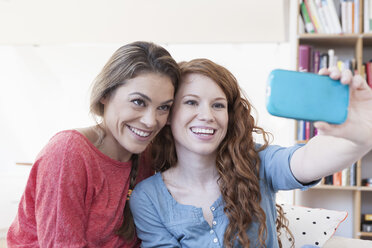 Two young female friends taking a picture of themseves with smartphone - RBF001575