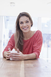 Young woman with cup of coffee sitting at table at home - RBF001578
