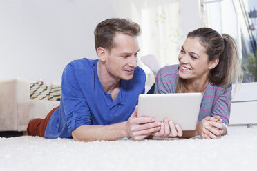 Couple at home lying on carpet and using tablet computer - RBF001503