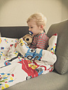 Little boy sick, sitting on couch with sleeping gear - MEAF000056