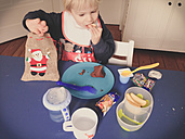 Child eating Christmas candy and breakfast at the sametime, Bonn, North Rhine-Westphalia, Germany - MEA000014