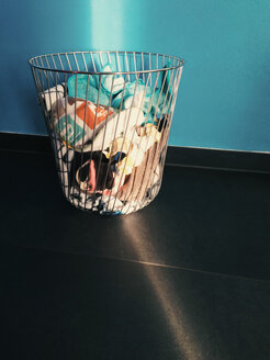 Laundry basket being hit by ray of sunlight in front of a blue wall - MEAF000062