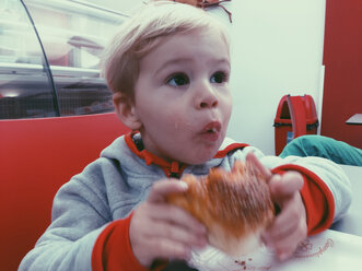 Young boy eating a bun in a restaurant of Palermo, Sicily, Italy - MEAF000081