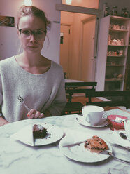 Young woman at coffee and cake table, looking at camera, Palermo, Sicily, Italy - MEAF000088
