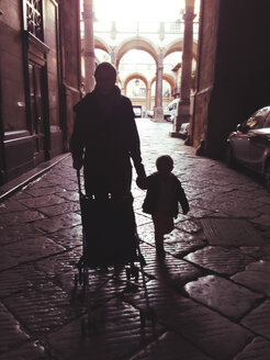 Silhouettes of mother and son walking in a palazzo of Palermo, Sicily, Italy - MEAF000075