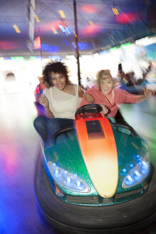 Germany, Herne, Two young women riding bumper cars at the fairground - BGF000067