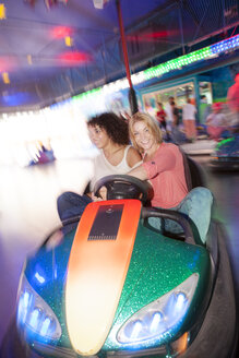 Germany, Herne, Two young women riding bumper cars at the fairground - BGF000066