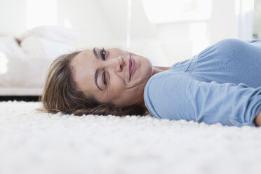 Woman lying on carpet twinkling - RBF001500